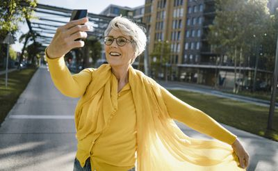 A woman in a yellow top taking a slow motion selfie/slofie on her iPhone.
