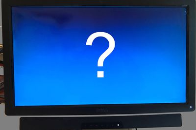 Screen with question mark on it, blue background, surrounded by grey, and cables visible in background