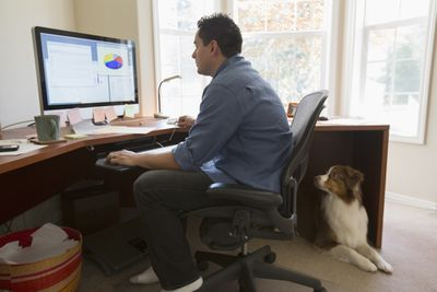 Telecommuter at desk with computer and dog