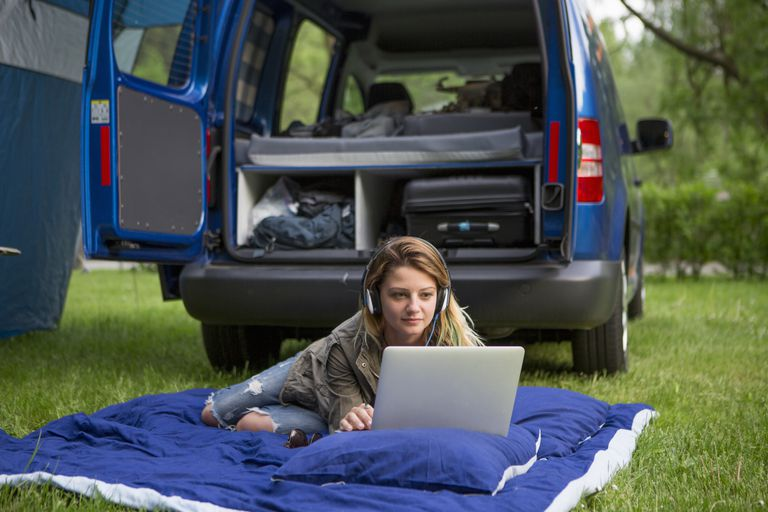 woman using car power to charge laptop on camping trip
