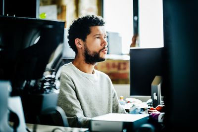 A man sitting at a desk looking at a computer screen
