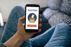 Mobile phone showing the words 'election' and 'vote now' on the screen