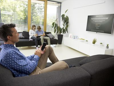 A man sitting on a lounge casting his Android smartphone to the Fire Stick connected to his TV.