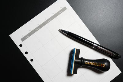 Business planning cancelled with blank calendar, pen and cancelled rubber stamp on black background
