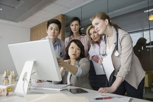 Medical personnel looking at a Mac