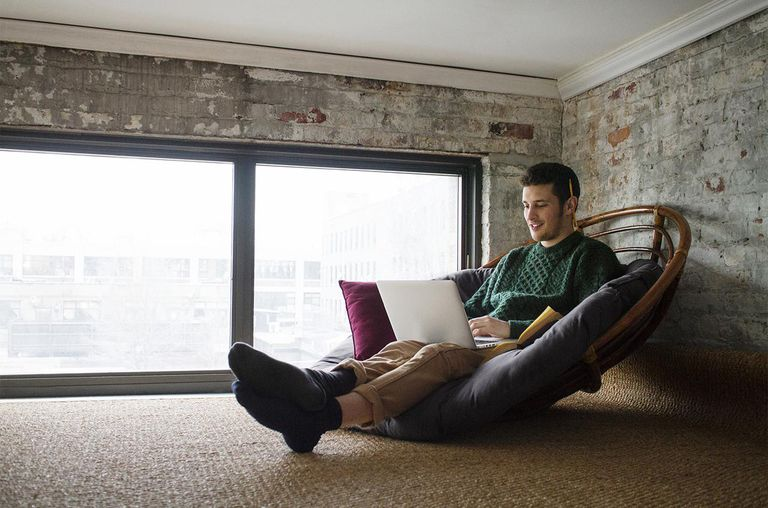 Young Man Using a Laptop in a Loft Apartment