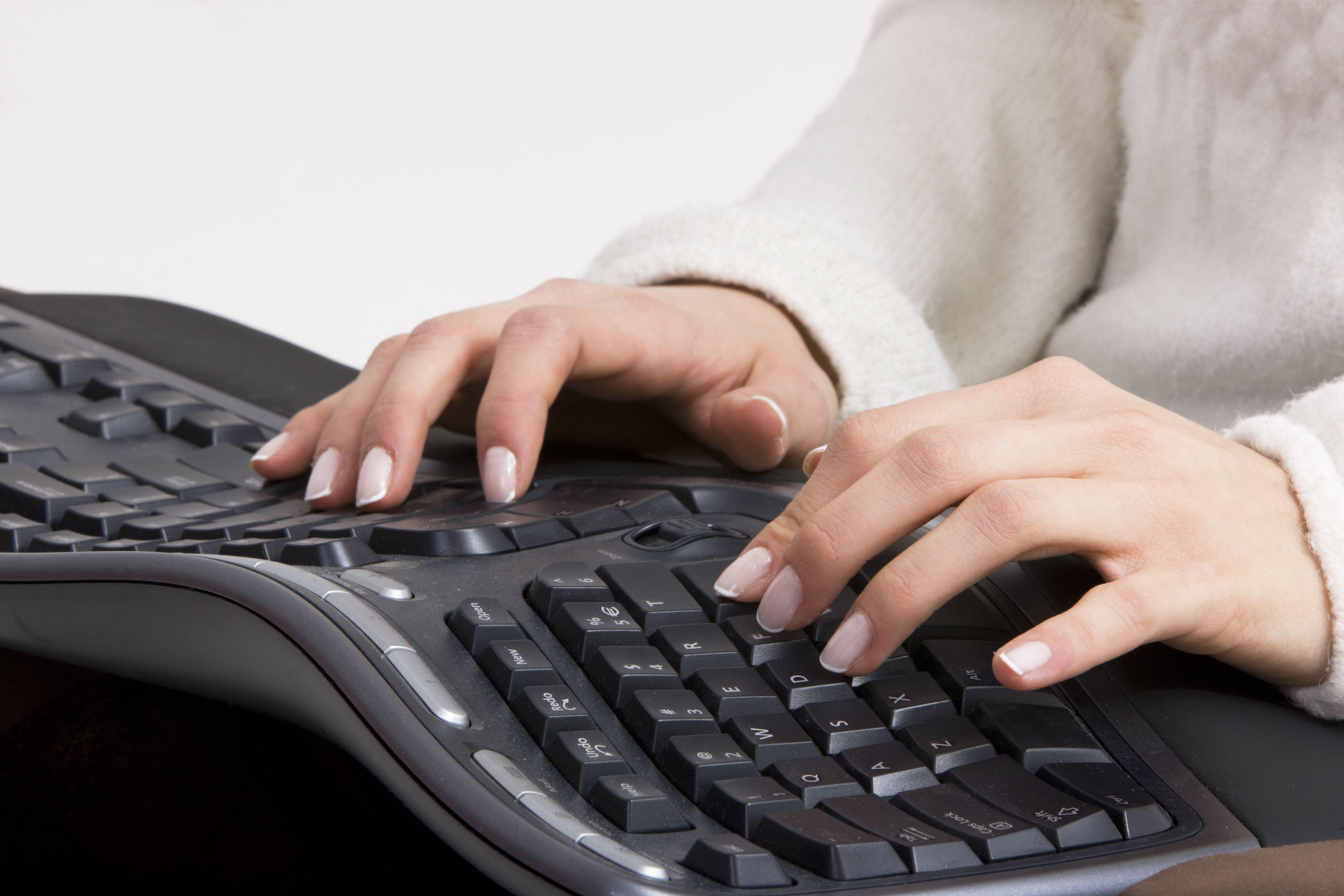 hands typing on ergonomic keyboard