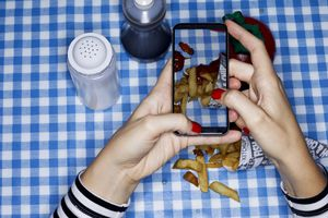 Snapping a mobile photo of french fries on a blue checkered table