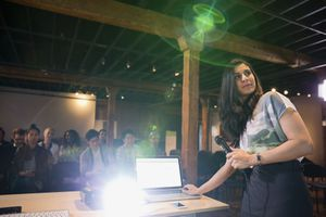 A woman using a laptop and projector.