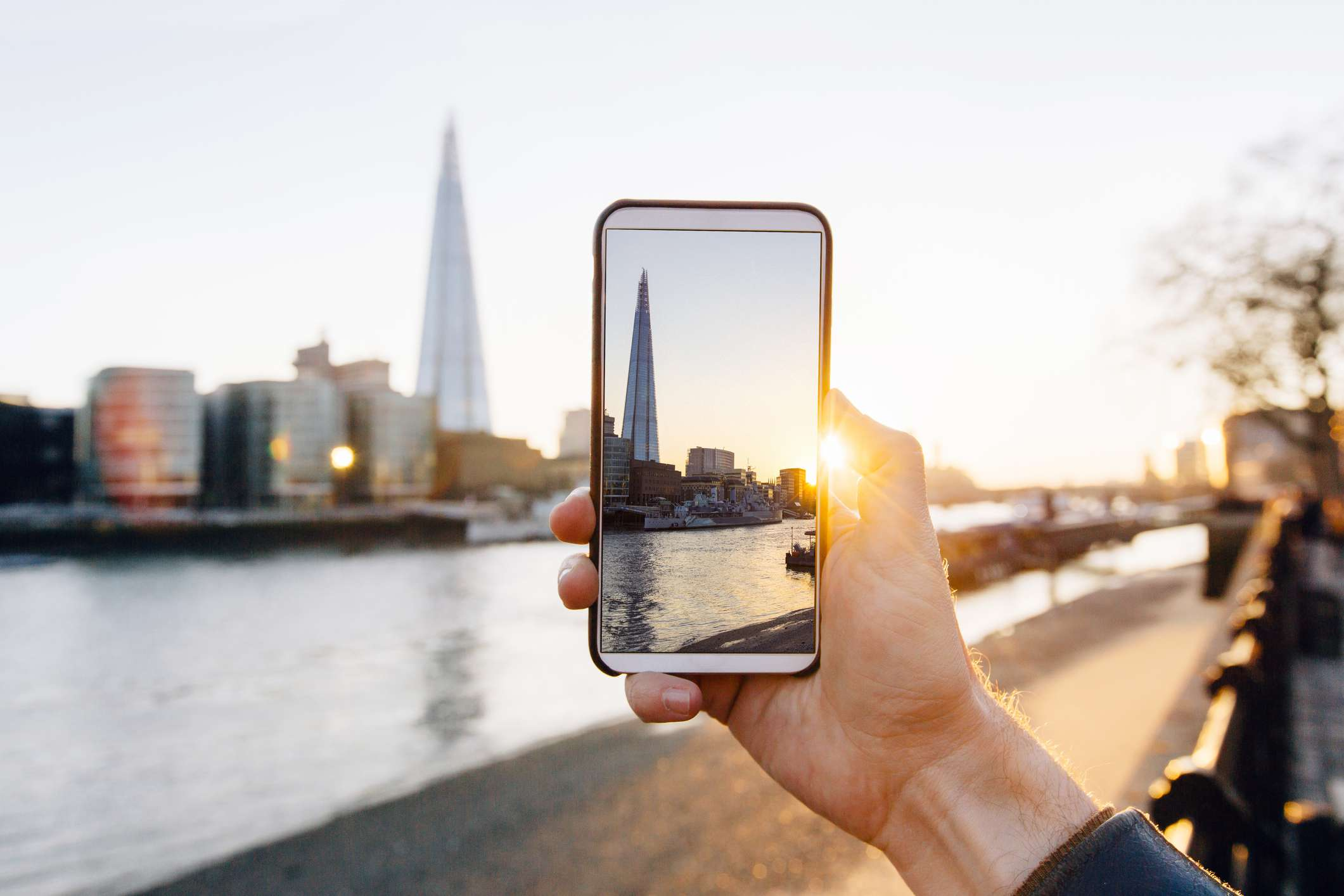 Someone taking pictures of the London skyline at sunset with a smart phone.