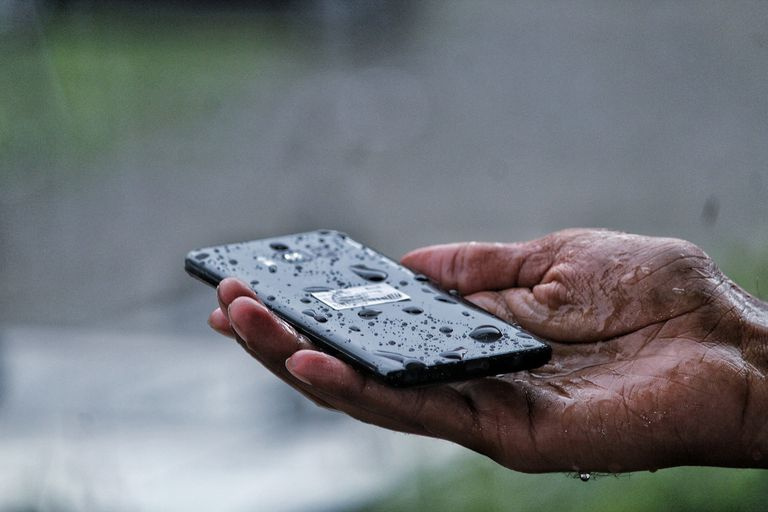 A hand holding a wet smartphone in their palm.