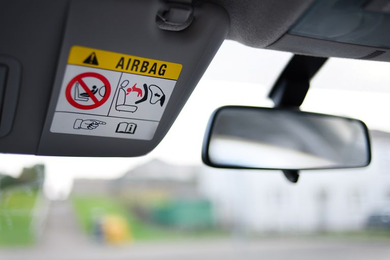 Airbag warning label on sun visor next to rear view mirror