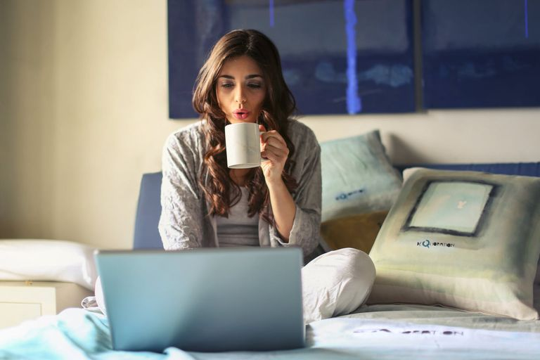 woman in bed with coffee reading laptop
