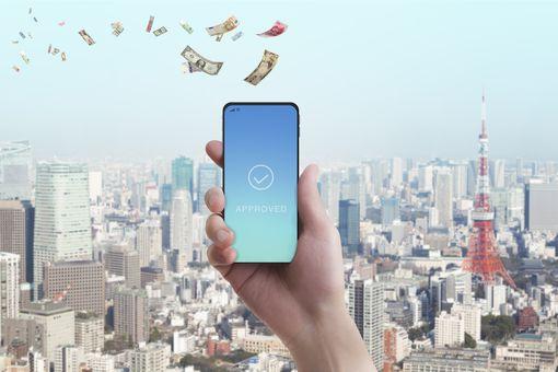 A hand holding a smartphone as money flies away.