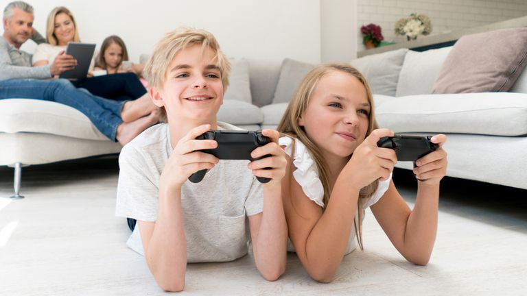 A boy and girl playing offline video games on their Xbox One gaming console.