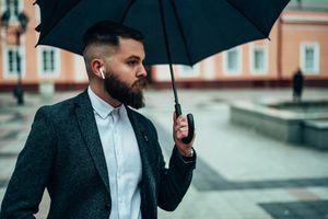 A man wears AirPods in the rain.