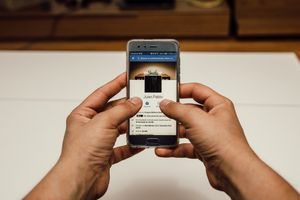 An image of a man looking at a Facebook profile on a smartphone.