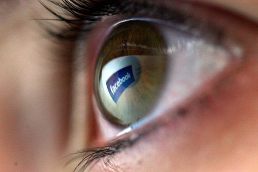 Close up of an eye with the Facebook logo reflected in it