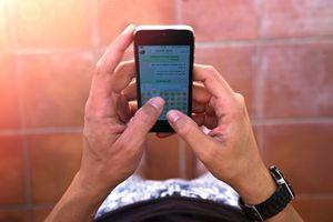 Closeup of someone texting using Emoji.