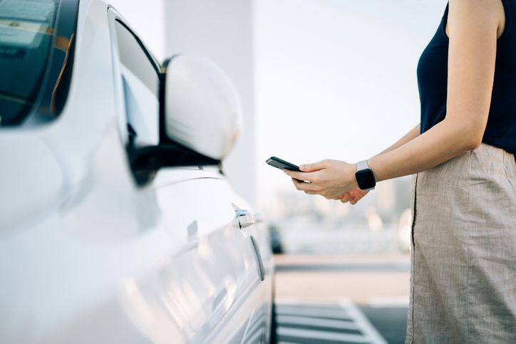 person using mobile app device on smartphone to unlock the doors of her car in a car park