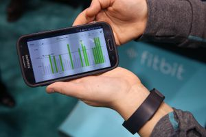 Data collected from the Fitbit Force is displayed on a smartphone