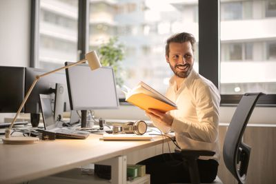Man with book, laptop and desktop monitor