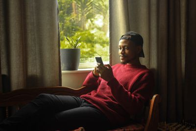 A man sitting near a bright window looking at his phone