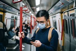 A commuter using a smartphone on a subway wearing a face mask.