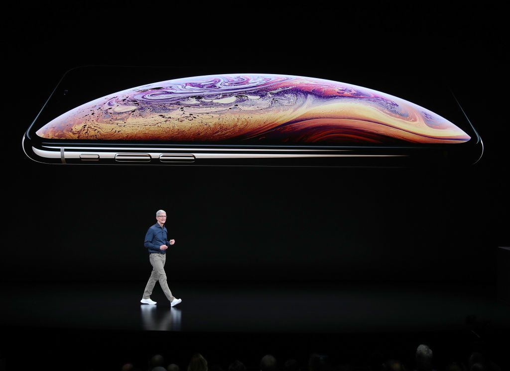 Tim Cook walking on stage in front of iPhone XS during an announcement.
