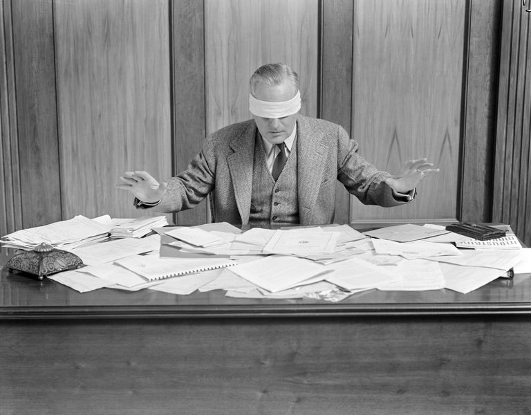 Blindfolded Businessman At Desk Covered With Paper