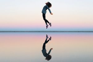 A mirrored image of a woman jumping.