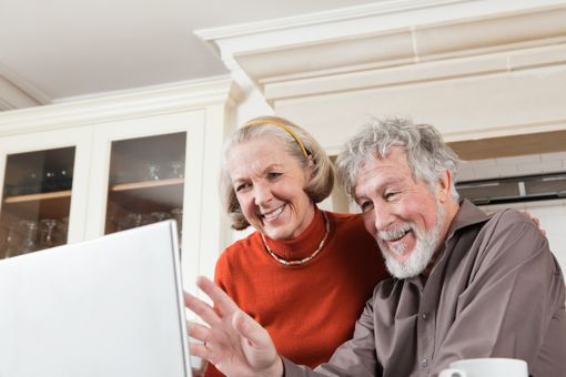 Senior couple using webcam on laptop