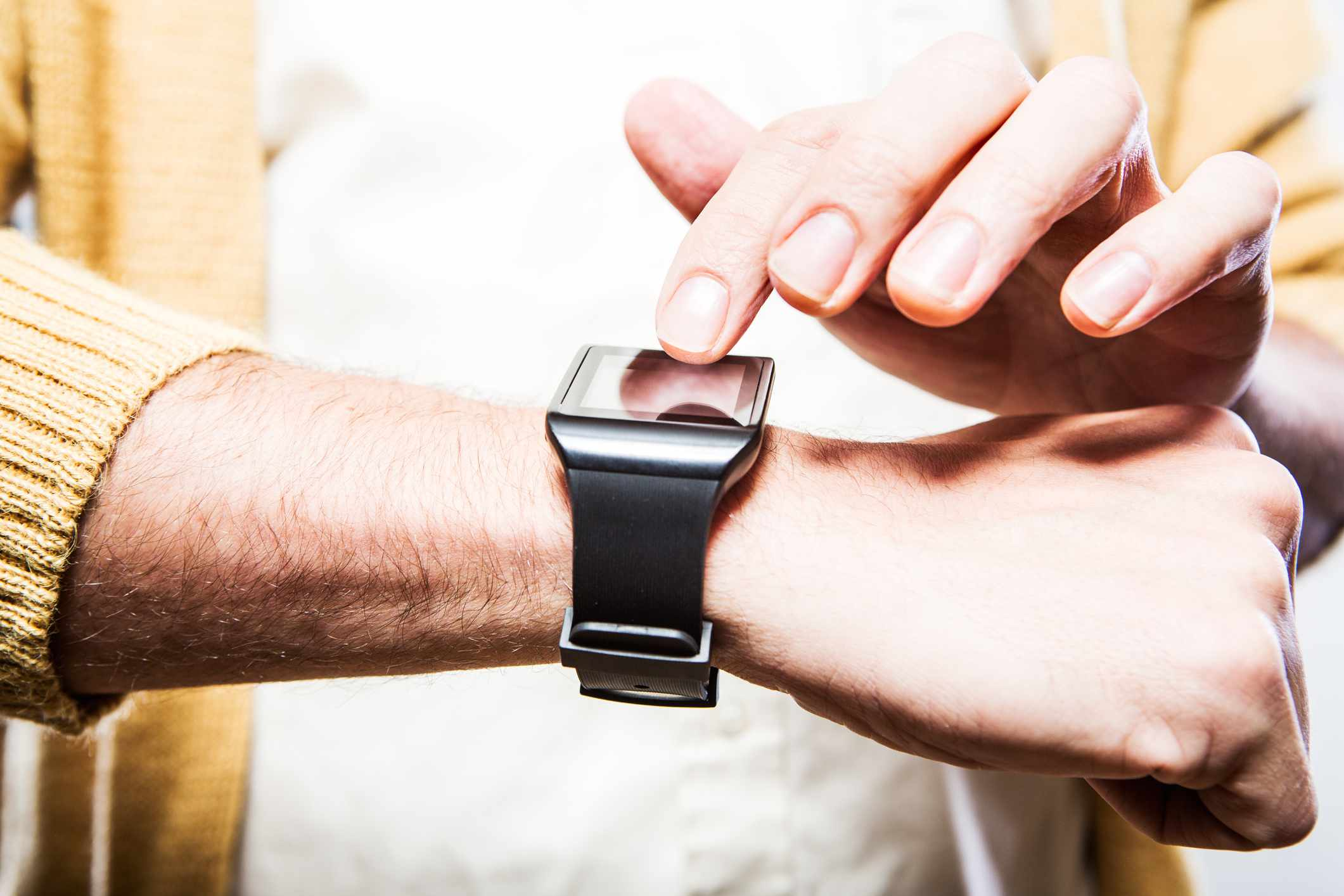 man tries out a generic but modern looking touch screen smart-watch on his wrist