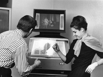 Couple dancing in front of a vintage TV/jukebox