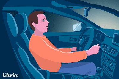 Image of a worried-looking person in a car without lights
