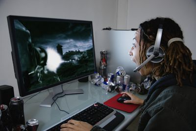Person playing a desktop computer game, side view