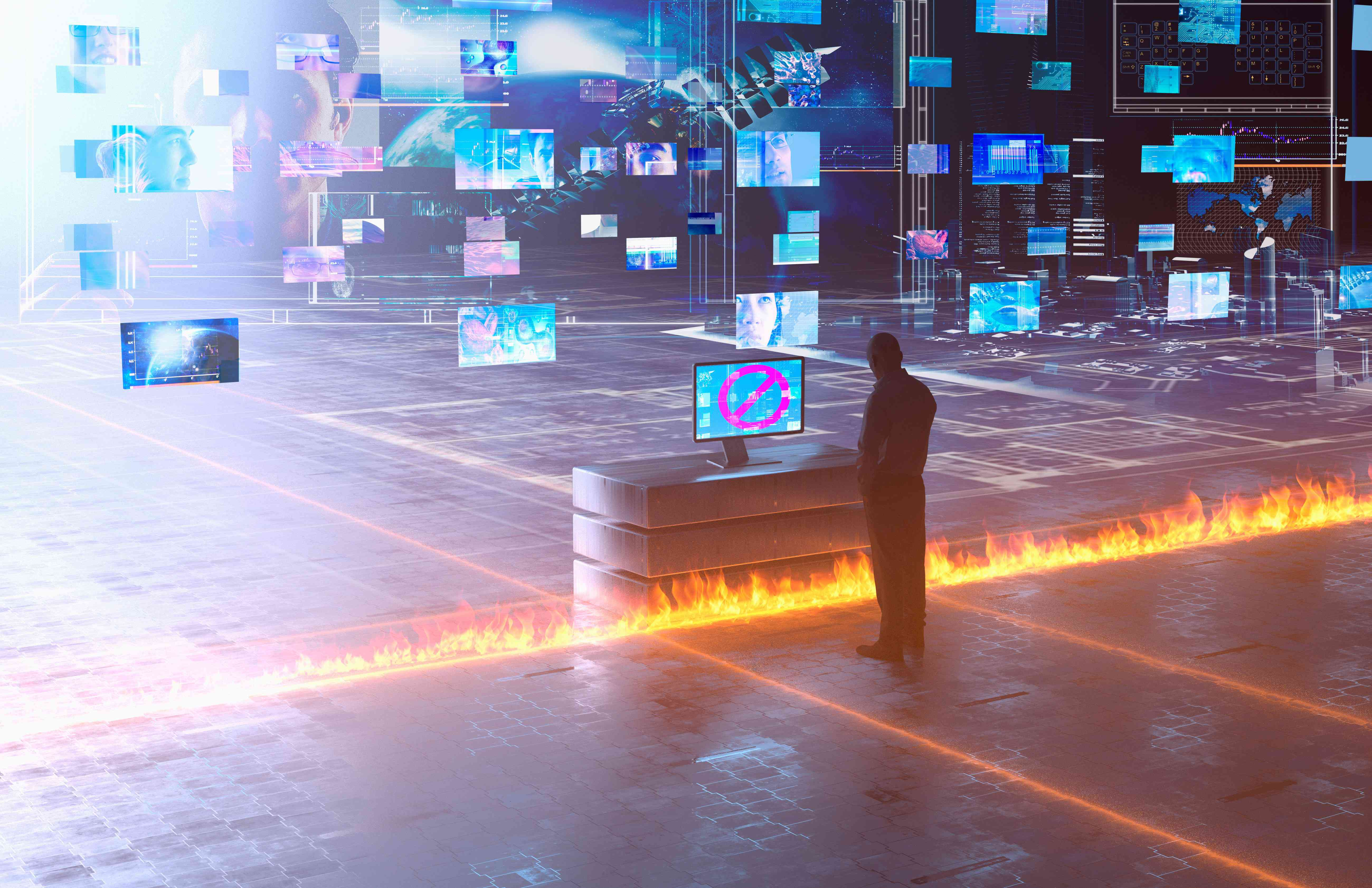 Person standing in front of several computer monitors with a fire between them.