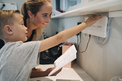 A parent and child installing a wireless router.
