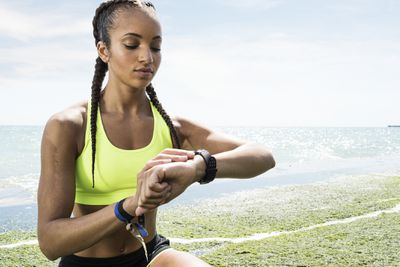 Young female runner looking at fitness tracker