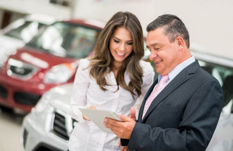 Photo of woman and man looking at tablet with cars in the background.