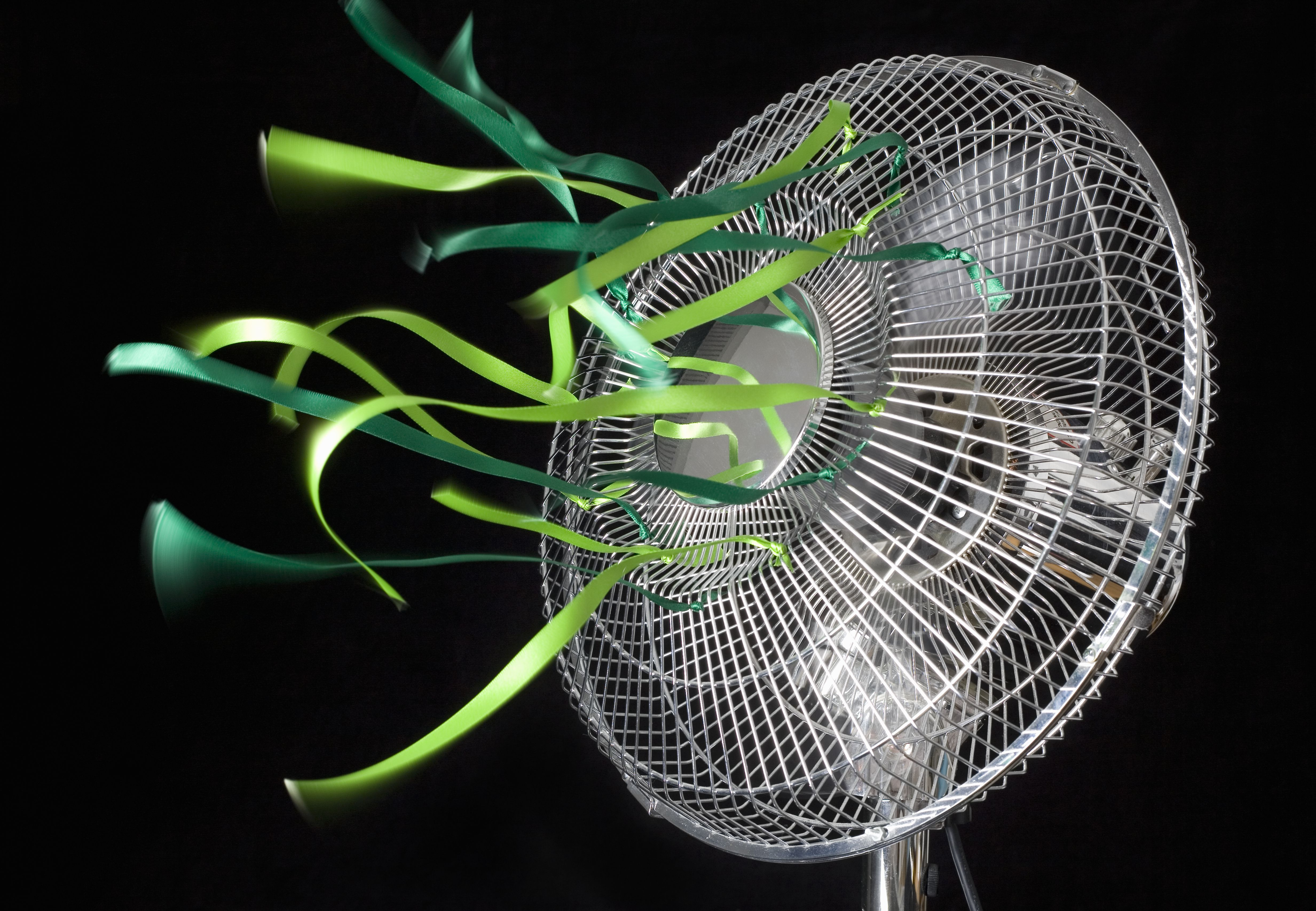 Green ribbons flying on an electrical fan