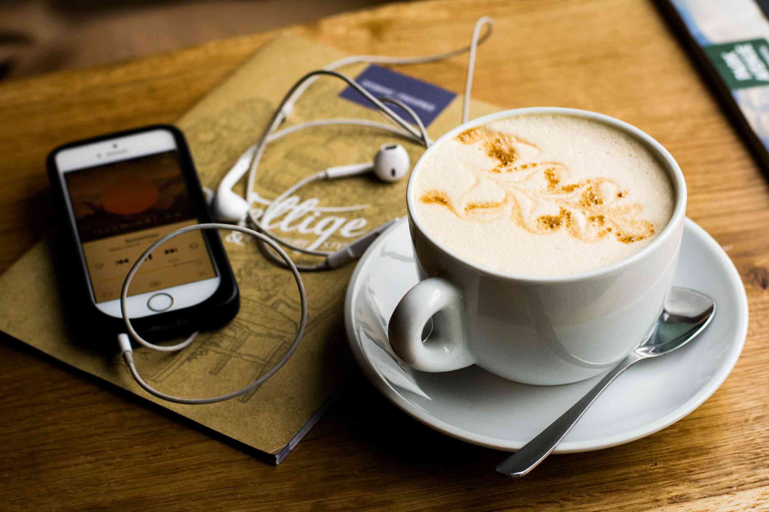 An iPhone displaying a podcast, connected to wired headphone with a travel journal and a cup of café coffee nearby.