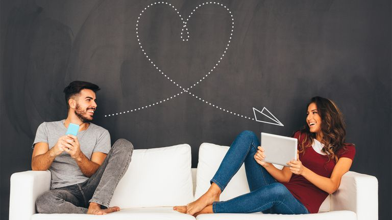 Man and woman sitting on a white couch smiling at each other while holding devices.