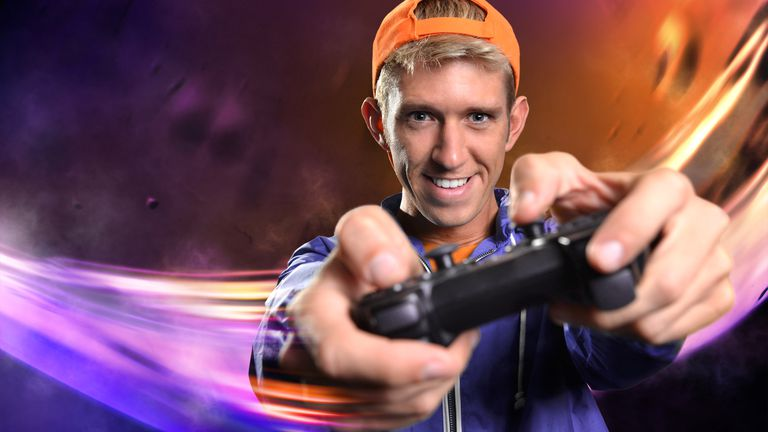 White man wearing an orange cap and purple jumper playing video games on a Sony PlayStation 4