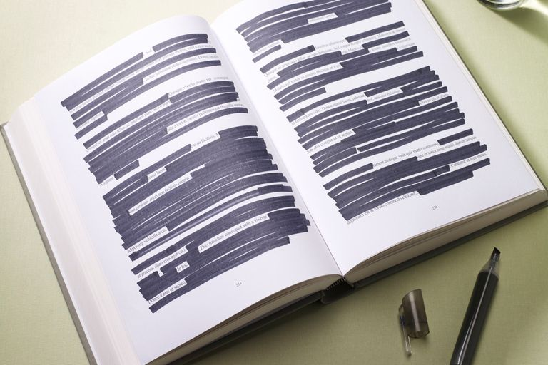 An open book with a lot of the text blacked out with a marker