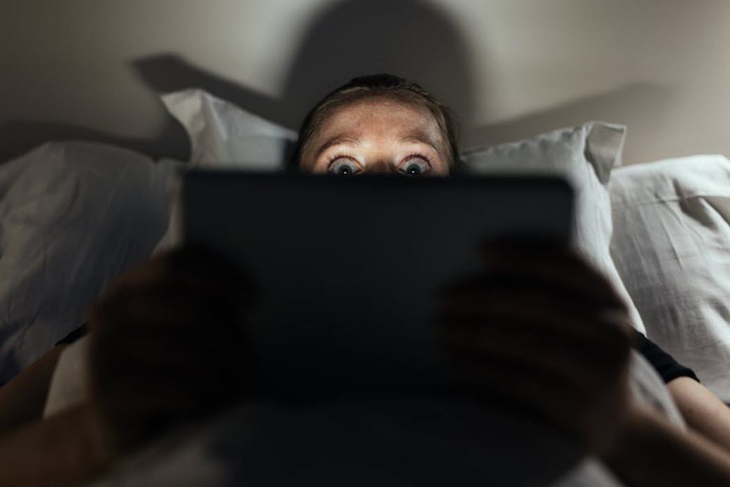 A person laying in bed watching something scary on their tablet.