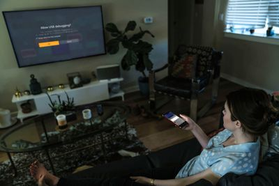 A woman sideloads a Fire TV device from her phone.