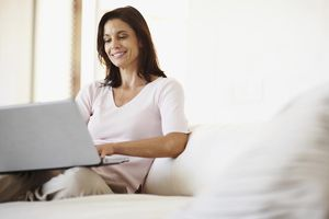 Smiling business woman with laptop sitting on couch