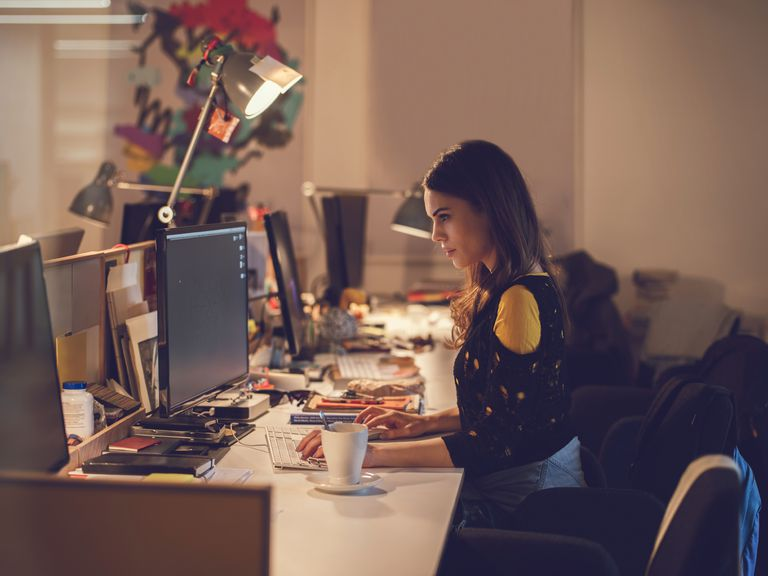 Side view of a young woman working on a computer.