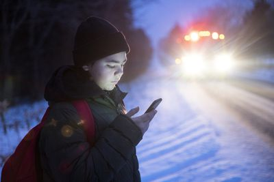 A teenager using a smart phone to connect with his friends on social media while he waits for the school bus in the winter